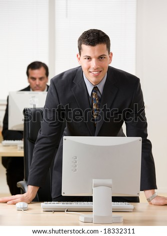 Confident young businessman leaning on desk over computer monitor - stock photo