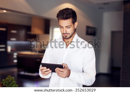 Confident young businessman reading news and messages on tablet at home - stock photo