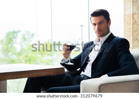 Confident young businessman sitting at restaurant with glass of wine - stock photo