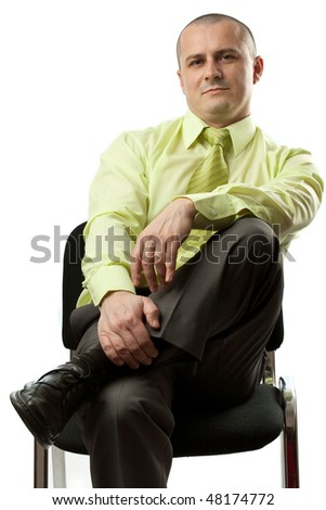 Confident young businessman sitting on chair, isolated on white background - stock photo