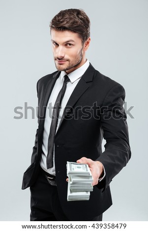 Confident young businessman standing and giving money to you over white background - stock photo
