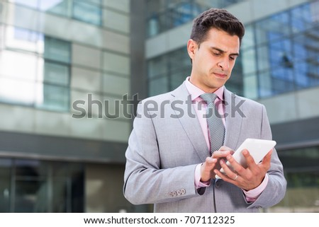 Confident young businessman standing on factory background and using cell phone