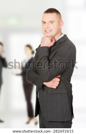 Confident young businessman with hand under chin - stock photo