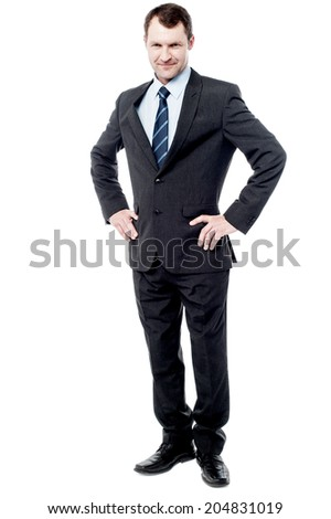 Confident young businessman with hands on his waist - stock photo