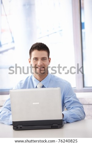 Confident young businessman working on laptop in bright office, smiling.? - stock photo