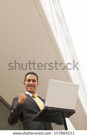 Confident young businessman working with his laptop at the office balcony