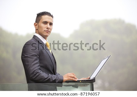 Confident young businessman working with his laptop at the office balcony - stock photo