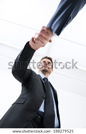 Confident young businessmen shaking hands bottom view. - stock photo