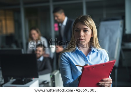 Confident young businesswoman holding a documents in an office. - stock photo