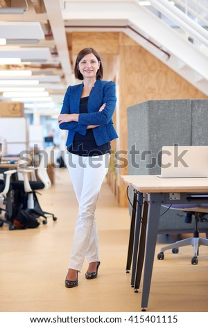 Confident young businesswoman standing in shared office space - stock photo