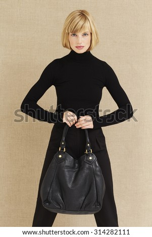 Confident young businesswoman with bag, portrait - stock photo