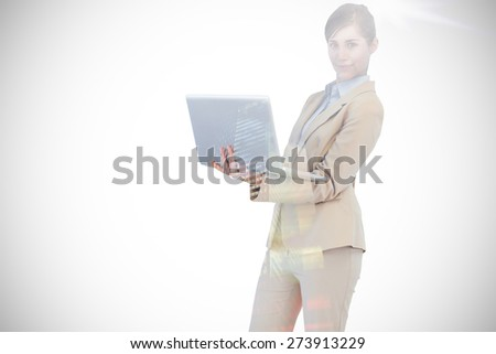 Confident young businesswoman with laptop against low angle view of skyscrapers at sunset - stock photo