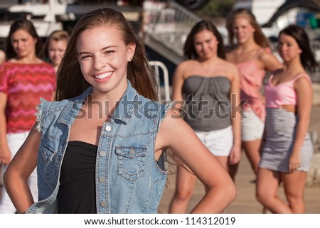 Confident young Caucasian girl in front of jealous friends - stock photo