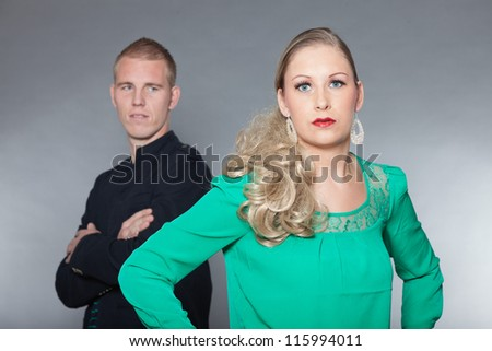Confident young couple. Man blurred in background. Cool looking. Chic dressed. Dark jacket. Green shirt. Jeans. Man short blonde hair. Woman long brown hair. Studio shot isolated on grey background. - stock photo