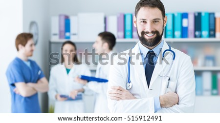 Confident young doctor posing in the office, he is smiling at camera with arms crossed, medical team on the background
