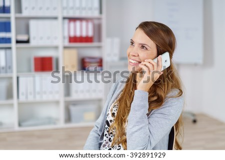 Confident young female adult in long hair and gray sweater smiling while talking on her cell phone in small office with chart and bookshelf in background