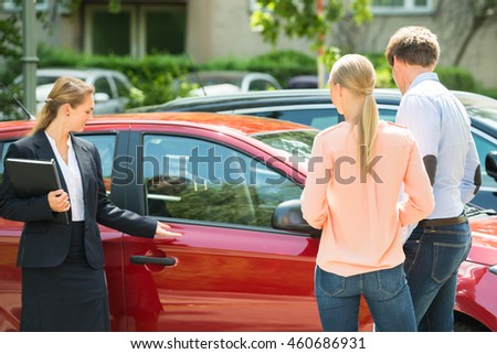 Confident Young Female Dealer Showing New Red Car To Couple