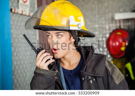 Confident young firewoman looking away while using walkie talkie at fire station - stock photo
