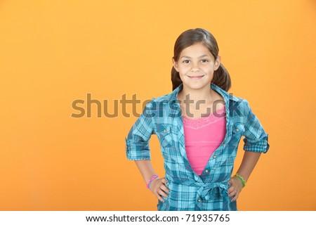 Confident Young Hispanic girl on orange background - stock photo