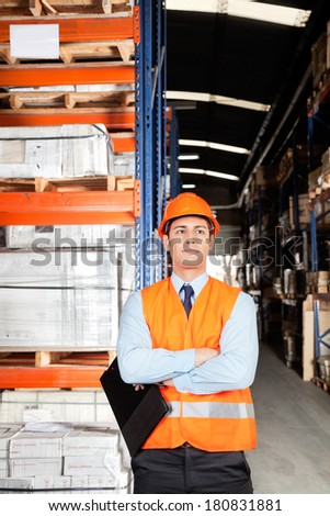 Confident young male supervisor in orange protective vest with arms crossed at warehouse - stock photo