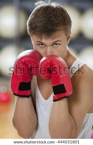 Confident Young Man Boxing In Gym - stock photo