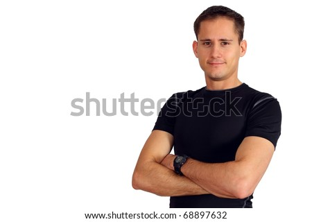Confident young man in a fitness T-shirt with his arms crossed - stock photo