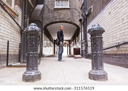 Confident young man in casual clothes standing in Urban surrounding in front of a passage in a ramshackle back alley. - stock photo