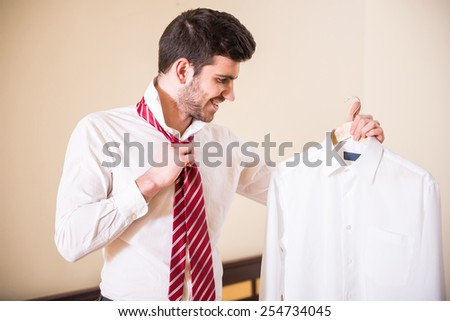 Confident young man in white shirt is tying his necktie and looking  at another shirt. - stock photo