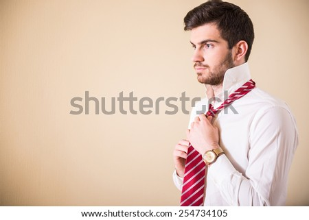 Confident young man in white shirt is tying his necktie and looking away. - stock photo