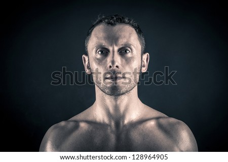 Confident young man shirtless portrait against black background. - stock photo