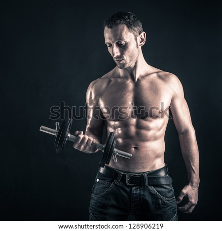 Confident young man shirtless portrait training with dumb-bell against black background.