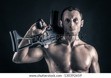 Confident young man shirtless portrait with machine gun against black background.