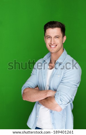 Confident young man with a friendly smile standing with folded arms against a green studio background looking at the camera