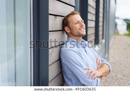 Confident young man with a satisfied expression and happy smile leaning back against the wall of his home daydreaming