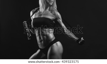 Confident young muscular fitness female looking away and posing with jumping rope in the studio on a black background. Front view of woman bodybuilder with jumping rope