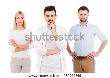 Confident young professionals. Three confident young people in smart casual wear looking at camera while standing against white background - stock photo