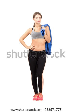 Confident young sporty woman holding towel over shoulder. Full body length portrait isolated over white background. - stock photo