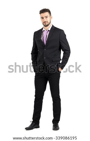 Confident young stylish man in suit looking at camera with hands in pockets. Full body length portrait isolated over white studio background.  - stock photo