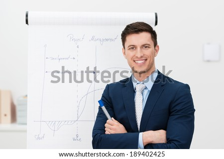 Confident young team leader or manager standing in front of a flip chart smiling at the camera with folded arms - stock photo