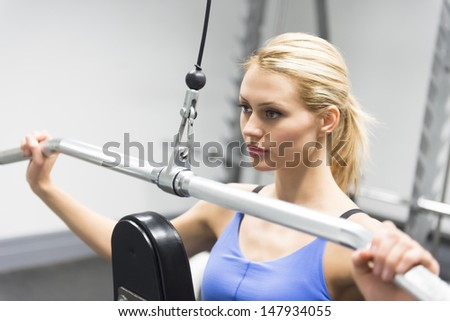 Confident young woman looking away while doing weight exercise at health club - stock photo