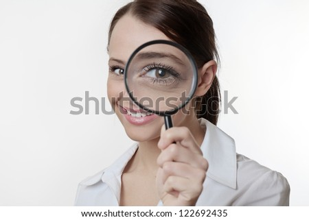 Confident young woman looking through a magnifying glass - stock photo