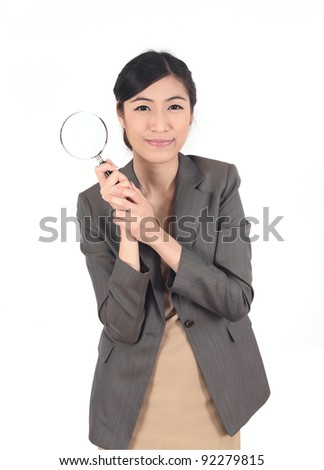 Confident young woman looking through a magnifying glass isolated - stock photo