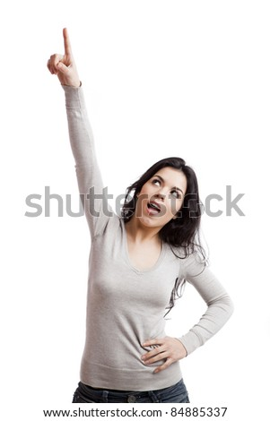 Confident young woman pointing to the air, isolated against white background - stock photo