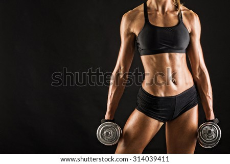 Confident young woman portrait training with dumb-bell against black background. Grunge effect. - stock photo