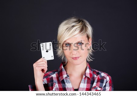 Confident young woman showing ace of hearts against black background - stock photo
