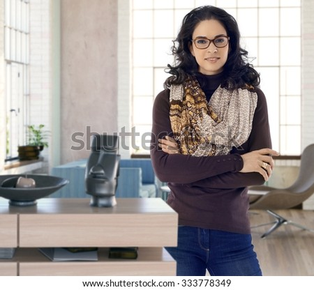 Confident young woman standing arms crossed at home, smiling. - stock photo