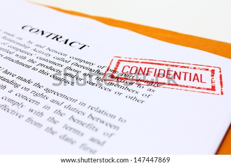 CONFIDENTIAL' Red Stamp over a business contract. - stock photo