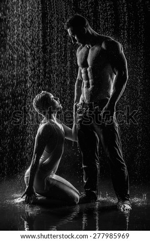 conflict and emotional stress in young people couple in rain - stock photo