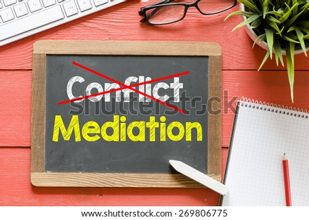 Conflict and mediation on blackboard. Conflict and mediation Handwritten with chalk on blackboard, keyboard,notebook,glasses and green plant on wooden background - stock photo