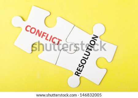 Conflict and resolution words printed on two pieces of puzzle - stock photo